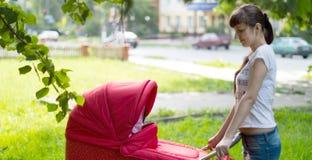Мать с красным экипажом для девушки на прогулке Стоковые Фотографии RF