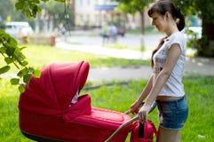 Мать с красным экипажом для девушки на прогулке Стоковые Изображения