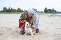 Мать с маленькими дочерью и щенком бульдога в осени outdoors Стоковое Изображение