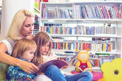 Мать с маленькой девочкой и мальчиком прочитала книгу совместно в салоне стоковые изображения rf