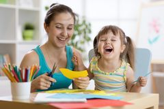 Мать с маленькой потехой дочери отрезала бумагу ножниц покрашенную Стоковая Фотография RF