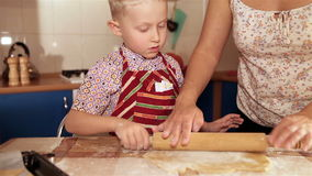 Мать с маленьким сыном замешивает тесто для пряника акции видеоматериалы