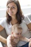Мать с младенцем на софе Стоковые Фотографии RF
