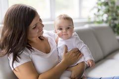 Мать с младенцем на софе Стоковые Изображения