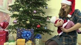 Мать с младенцем имеет потеху около ели и подарков на рождество видеоматериал