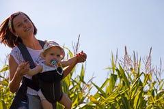 Мать с младенцем на кукурузном поле Стоковые Изображения