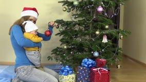 Мать с младенческим младенцем в ее игрушке рождественской елки вида рук акции видеоматериалы