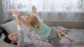 Мать с дочерью в спальне Сыграна девушка с ложью ребенка на кровати и Младенец в футболке  сток-видео