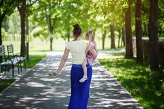 Мать с дочерью на руках идет в парк изолированная белизна вид сзади Стоковое Фото
