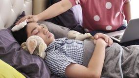 Мать с ребенком пробует работать на ноутбуке дома, больной мальчик лежала в кровати сток-видео
