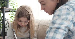 Мать с сочинительством маленькой девочки используя ручку дома сток-видео