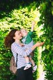 Мать с сыном в парке на времени весны на предпосылке gree стоковое изображение rf