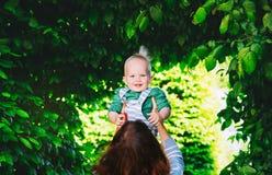 Мать с сыном в парке на времени весны на предпосылке gree стоковые изображения rf