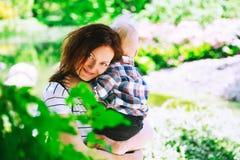 Мать с сыном в парке на времени весны на предпосылке gree стоковые фотографии rf