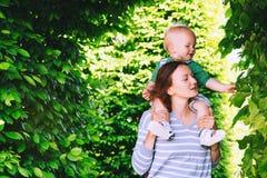 Мать с сыном в парке на времени весны на предпосылке gree стоковые фото