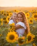 Мать с сыном младенца в поле солнцецвета Стоковое фото RF