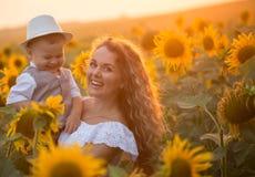 Мать с сыном младенца в поле солнцецвета Стоковая Фотография RF