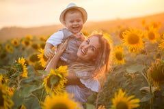 Мать с сыном младенца в поле солнцецвета Стоковая Фотография