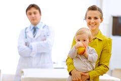 мать удерживания доктора младенца яблока Стоковое Фото