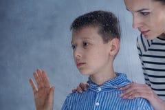 Мать утешает ее аутистического сына стоковая фотография