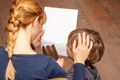 Мать утешая сына держа пустой лист в ее руке стоковое изображение