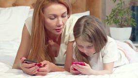 Мать уча ее дочери используя умный телефон сток-видео