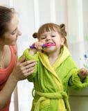 Мать учит ее маленькой дочери как почистить зубы щеткой стоковые изображения rf