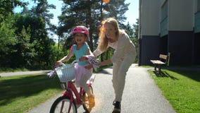 Мать учит, что ее дочь едет велосипед видеоматериал