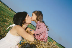 Мать целуя ее дочь в поле Стоковые Фото