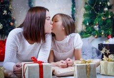 Мать целуя дочь на щеке на рождестве стоковые фотографии rf