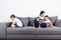 Мать читает интересную книгу с ее сыновььями Концепция ревности Стоковое Фото