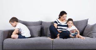 Мать читает интересную книгу с ее сыновььями Концепция ревности Стоковые Фотографии RF