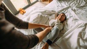 Мать щекоча ее мальчика на кровати стоковая фотография rf