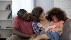 Мать щекоча и забавляя ее маленькую дочь, счастливую семью сидя на кресле стоковые фото
