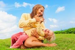 Мать щекоча смешной сына младенца лежа на ее подолах Стоковое Изображение RF