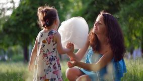 мать 4K и ребенок в парке едят зубочистку конфеты сток-видео