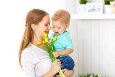 мать s дня счастливая Сын младенца дает цветки для мамы Стоковое Изображение