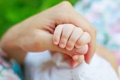 мать s удерживания руки младенца Стоковая Фотография RF