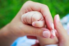 мать s удерживания руки младенца Стоковая Фотография