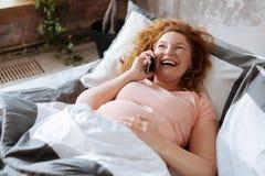 Мат-к-говорите на телефоне в кровати и смеяться над Стоковые Изображения RF