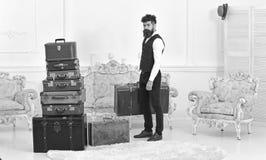Мачо элегантное на строгой стороне носит винтажный чемодан Багаж и концепция перестановки Человек, дворецкий с бородой и стоковое фото rf