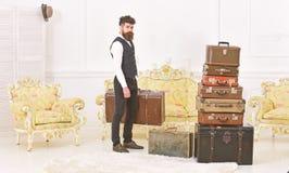 Мачо элегантное на строгой стороне носит винтажный чемодан Багаж и концепция перестановки Человек, дворецкий с бородой и стоковая фотография