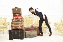 Мачо элегантное на строгой стороне носит винтажный чемодан Человек, дворецкий с бородой и усик нося классический костюм поставляю стоковое фото
