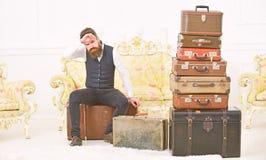 Мачо элегантное на строгой стороне сидит утомленная близко куча винтажного чемодана Человек, дворецкий с бородой и усик поставляю стоковое фото rf