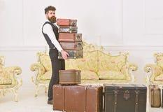 Мачо, элегантный портер на строгой стороне носит кучу винтажных чемоданов Батлер и концепция обслуживания Человек с бородой и стоковое фото rf