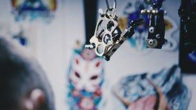 Машина для татуировки висит на держателе акции видеоматериалы