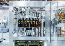 Машина завалки льет пиво в пластичные бутылки ЛЮБИМЧИКА Стоковое фото RF