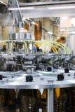 Машина завалки льет пиво в пластичные бутылки ЛЮБИМЧИКА Стоковое Изображение RF