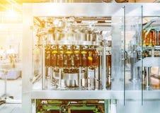 Машина завалки льет пиво в пластичные бутылки ЛЮБИМЧИКА Стоковое Изображение