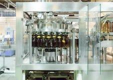 Машина завалки льет пиво в пластичные бутылки ЛЮБИМЧИКА Стоковые Изображения